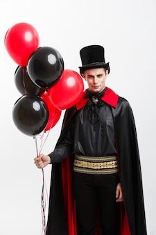 Концепция хэллоуина вампиров - полная длина портрет красивого кавказского вампира в черно-красном костюме хэллоуина.