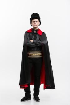 吸血鬼のハロウィーンの概念-黒と赤のハロウィーンの衣装でハンサムな白人の吸血鬼の完全な長さの肖像画。