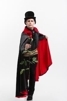 吸血鬼のハロウィーンの概念-赤いバラを与えるハンサムな白人の吸血鬼の完全な長さの肖像画。