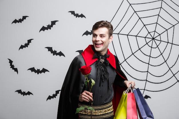 Концепция хэллоуина вампира - счастливый красивый кавказский вампир, держащий красочную хозяйственную сумку.
