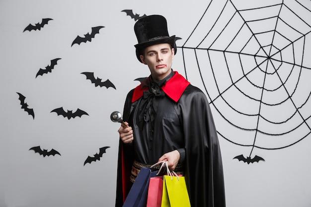 吸血鬼のハロウィーンのコンセプト-カラフルなショッピングバッグを保持している幸せなハンサムな白人の吸血鬼。
