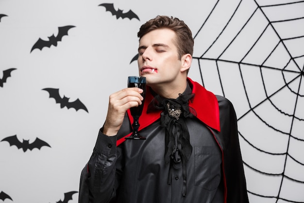 Vampire halloween concept - portrait of handsome caucasian vampire enjoy drinking bloody red wine.