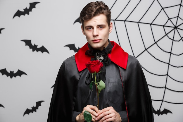 Vampire halloween concept - portrait of handsome caucasian vampire holding red beautiful rose.