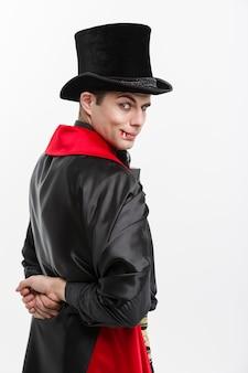 Концепция хэллоуина вампира - портрет красивого кавказского вампира вида сзади в черном и красном костюме хэллоуина, изолированном на белом.