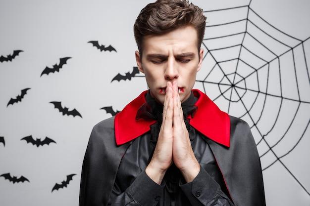Концепция хэллоуина вампира - портрет красивого кавказца в молящемся костюме вампира на хэллоуин.