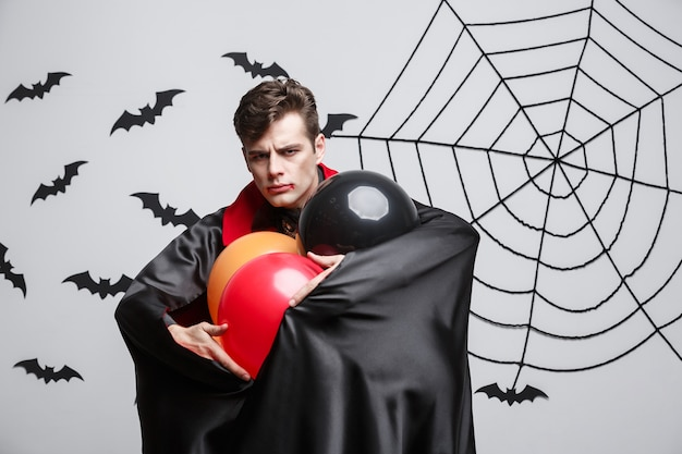 吸血鬼のハロウィーンの概念-カラフルなバルーンと吸血鬼のハロウィーンの衣装でハンサムな白人の肖像画。