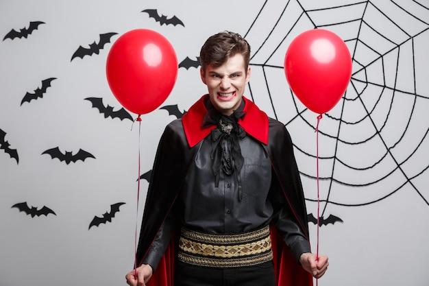 Концепция хэллоуина вампира - портрет красивого кавказца в костюме вампира на хэллоуин с красочным воздушным шаром.