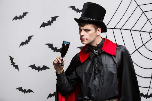 Концепция хэллоуина вампиров - портрет красивого кавказского вампира нравится пить кровавое красное вино.