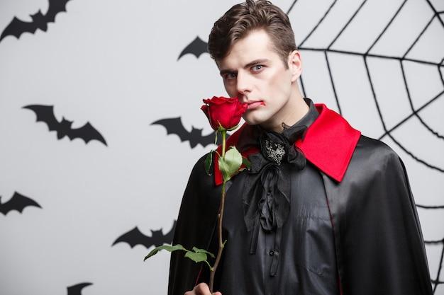 뱀파이어 할로윈 개념-빨간색 아름 다운 장미를 들고 잘 생긴 백인 뱀파이어의 초상화.