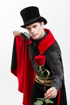 吸血鬼のハロウィーンの概念-赤い美しいバラを保持しているハンサムな白人の吸血鬼の肖像画。 Premium写真