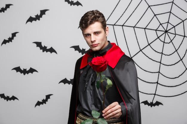 吸血鬼のハロウィーンの概念-赤い美しいバラを保持しているハンサムな白人の吸血鬼の肖像画。