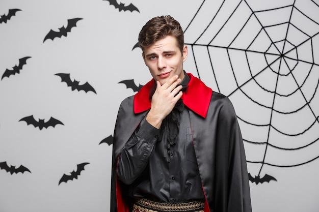 吸血鬼のハロウィーンの概念-黒と赤のハロウィーンの衣装でハンサムな白人の吸血鬼の肖像画。