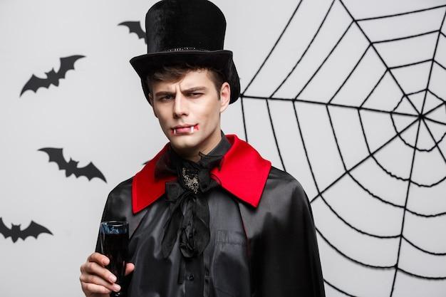 Концепция хэллоуина вампиров - портрет серьезного красивого кавказского вампира наслаждается питьем кровавого красного вина.