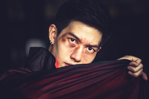 黒のハロウィーンの衣装で血を持つ吸血鬼男。ハロウィーンの概念。