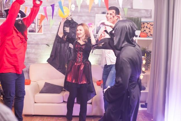 友達とハロウィンを祝いながら笑う吸血鬼の女。