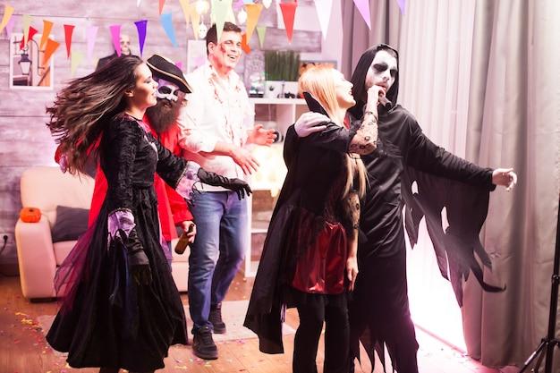 Vampire woman and grim reaper doing karaoke while celebrating halloween.