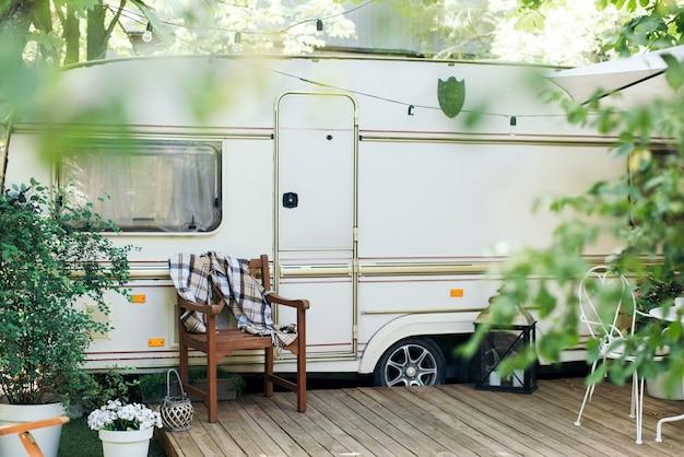 테라스가있는 밴 이동 주택, 바퀴 달린 집. 캐러밴 캠핑. 녹색 숲 정원에서 바퀴에 트레일러 하우스. 트레일러