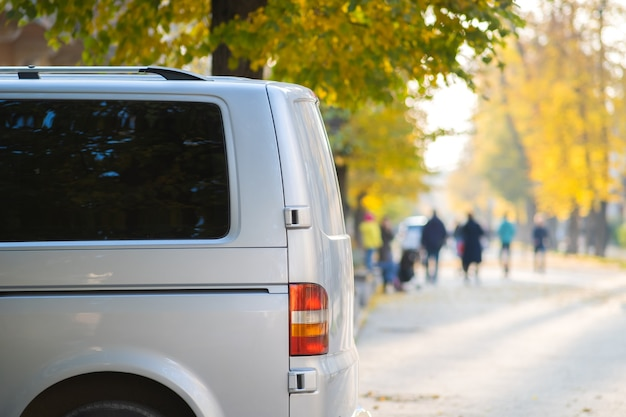 Van parked on a city street side on bright autumn day with blurred people walking on pedestrian zone.