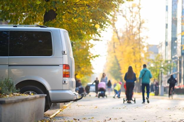 Фургон припарковался на обочине городской улицы в яркий осенний день с размытыми людьми, идущими по пешеходной зоне.