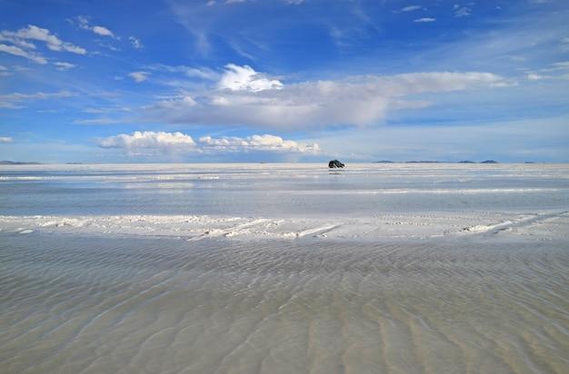 Van running on the shallow flooded areas of salar de uyuni or uyuni salts flats, bolivia