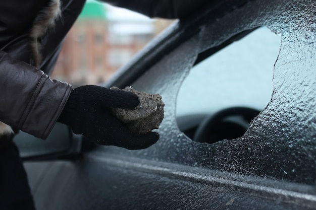 Vandalism winter man broke the glass of the car a little stone