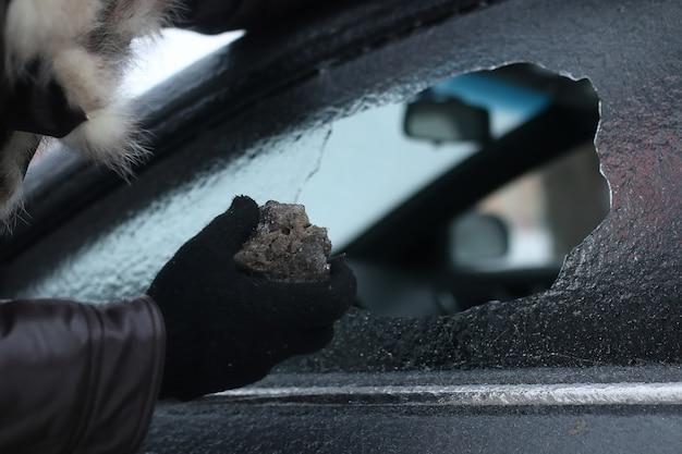 Вандализм зимой человек разбил стекло машины камешком