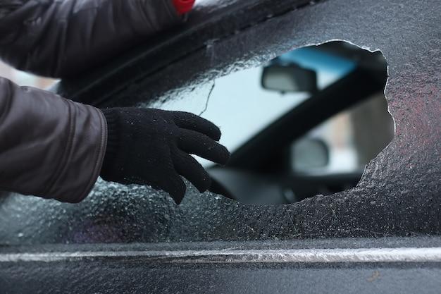 破壊行為の冬の男は車のガラスを小さな石を割った