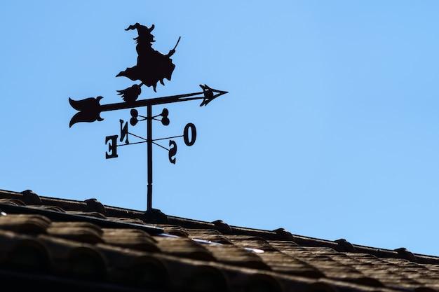 마녀와 바람의 방향을 가리키는 화살표가있는 야외 집 지붕에 베인. 스페인. 바람개비.