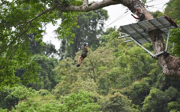 Vangviengラオスの森の中の大きな木にぶら下がっているジップラインエキサイティングなスポーツアドベンチャーアクティビティ