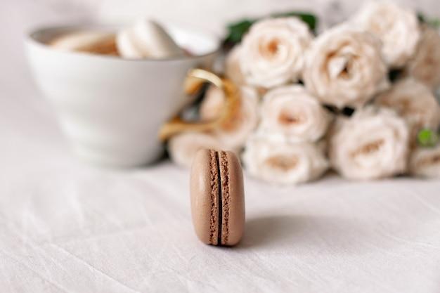 白いバラの背景にバニラとチョコレートのマカロン