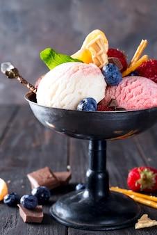 나무에 딸기와 금속 그릇에 바닐라와 딸기 맛 냉동 디저트 아이스크림