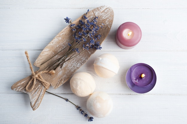 Vanilla aroma bath bombs in spa composition with dry lavender flowers and towels, flat lay