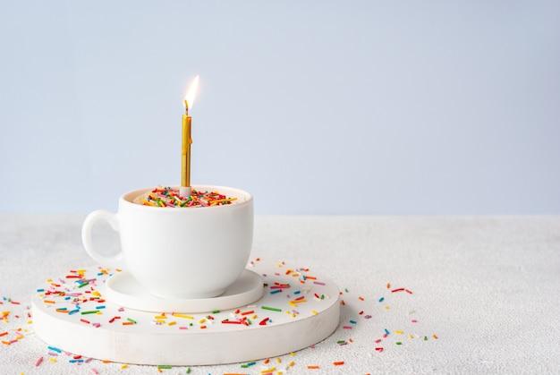 색 설탕 뿌리와 단일 불타는 초가있는 바닐라 생일 머그 케이크