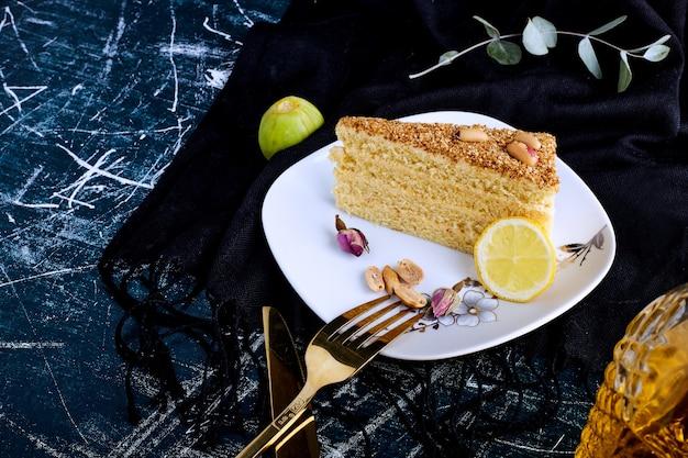 Torta alla vaniglia isolato su sfondo blu in un piatto bianco.