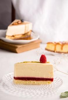 밝은 배경에 라즈베리 잼을 곁들인 바닐라 치즈 케이크와 다른 디저트 조각