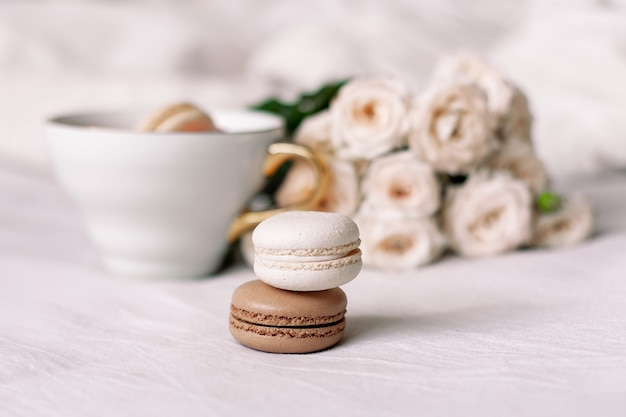 Vanilla and chocolate macaroons on white roses background