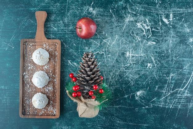 Dolci ricoperti di vaniglia su un piccolo vassoio, una mela e un ornamento natalizio sul blu.