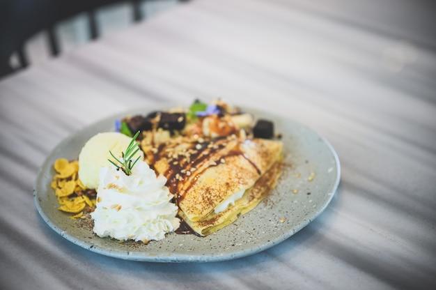 ブラウニー、アイスクリーム、チョコレートソース、甘い時間と軽食のデザート、ホイップクリーム、ベケリー、ペストリーを添えたバニラコールドクレープ。上面図