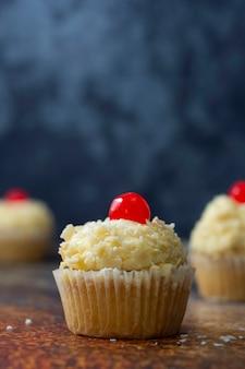 Ванильный кекс с масляным кремом и вишней сверху. синий фон. празднование, сладкая еда.