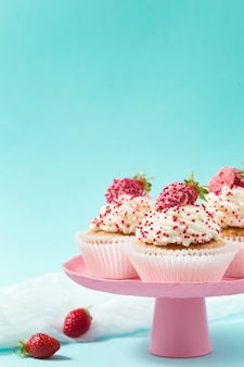 Vanilla cupcakes decorated strawberries on pink