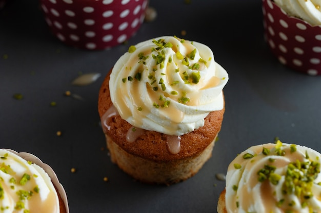 회색 테이블 배경에 크림과 카라멜 바닐라 컵 케이크.