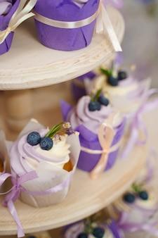 ラベンダークリームとバニラカップケーキ。テーママフィン。ブルーベリー、ローズマリー、花で飾られ、リボンで結ばれた紙のチューリップの形のクリームとカップケーキ。
