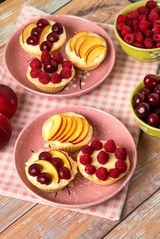 Cupcakes alla vaniglia con frutti di bosco estivi sui piatti rosa