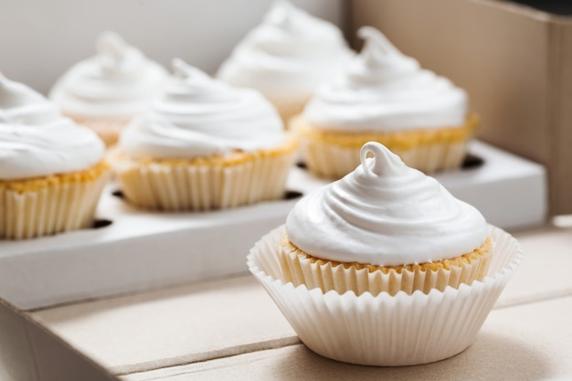 Vanilla cupcakes with white cream, cupcake packaging, delivery box, selective focus, close up