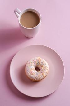 一杯のコーヒー、甘い艶をかけられたデザートフード、ピンクの最小限の背景、角度のビューに温かい飲み物の近くにプレートに振りかけるバニラドーナツ