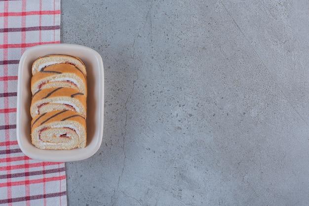 白いプレートにバニラ風味のスライスした甘いロールパン。