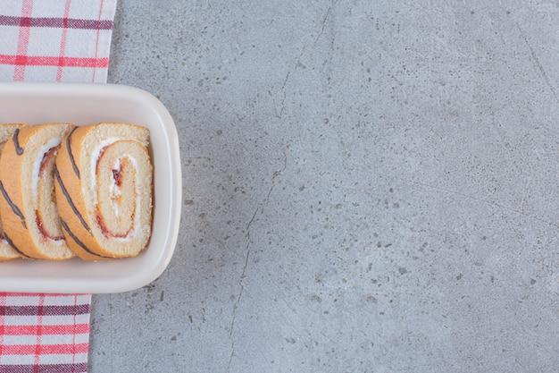白いプレートにバニラ風味のスライスした甘いロール。