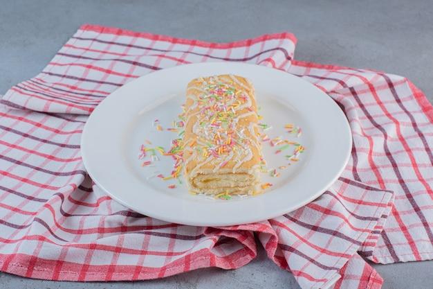 Rotolo dolce aromatizzato alla vaniglia decorato con spruzza sul piatto bianco.