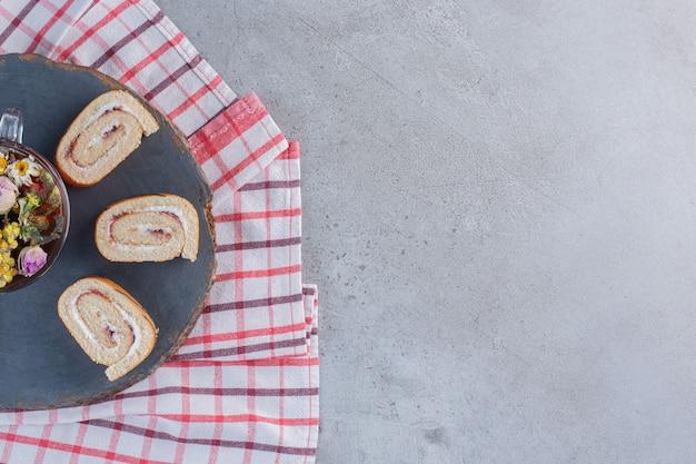 バニラ風味の甘いロールパンと一杯のお茶を木片に。