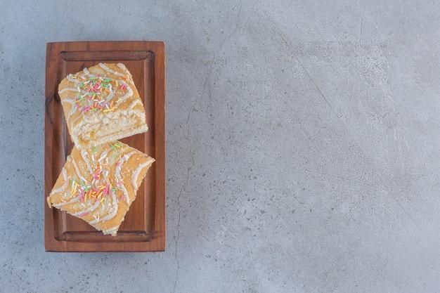 Vanilla flavored tasty sweet rolls on wooden board.